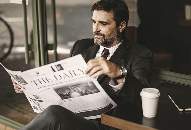 muž s kávou a novinami